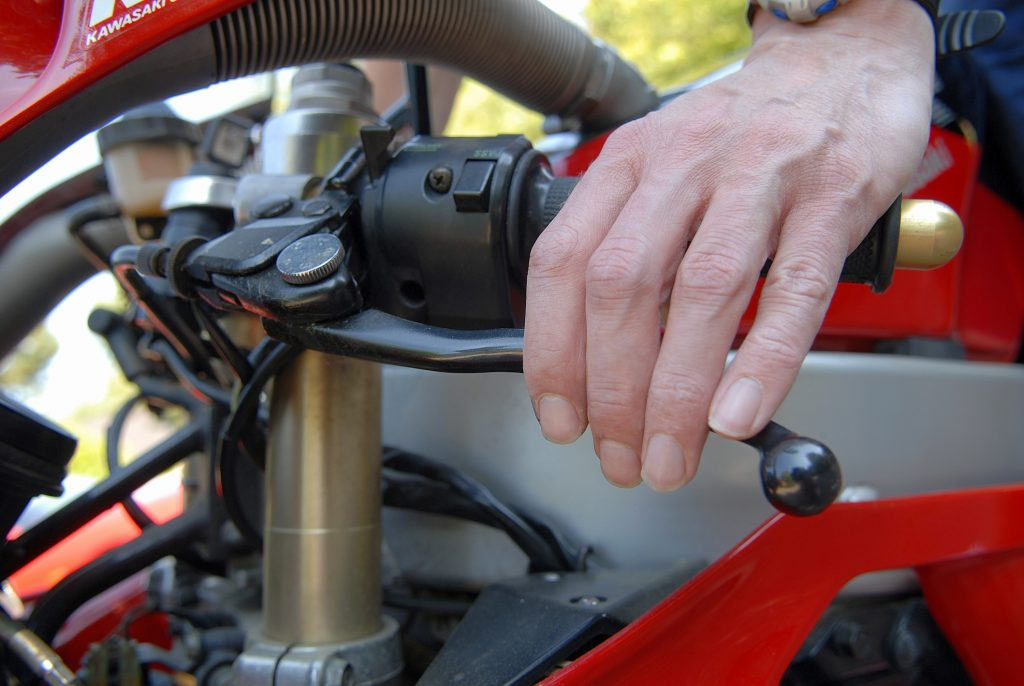 Close-up of man testing motorbike brakes